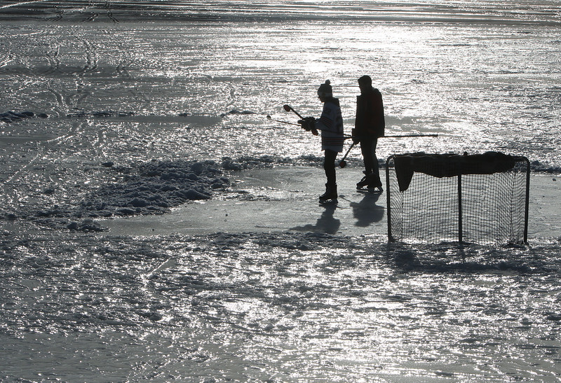 Features at frozen Long Lake in Littleton. Nathan LoConte, 14, of Westford, left, and his hockey friend Jack Borges, 14, of Littleton, move on to a larger smooth ice area on Long Lake. (SUN/Julia Malakie)