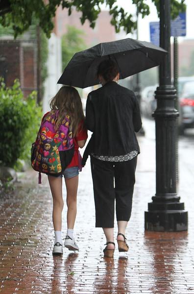 Nicole Burns of Dracut picks up her daughter Emerson Burns, 9, at Girls Inc. in Lowell, in a downpour.  (SUN/Julia Malakie)