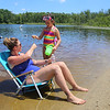 Chloe Swanson, 7, of Chelmsford, gives her mother Heather Swanson a water lily at Micozzi Beach in Billerica. (SUN/Julia Malakie)