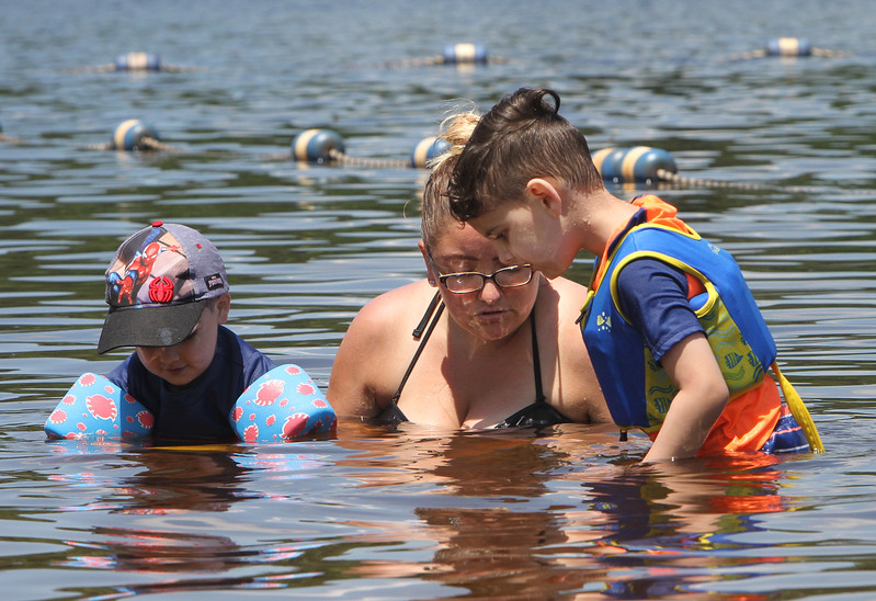Micozzi Beach in Billerica. Michelle Donofrio of Randolph and her friend's sons, Logan Costa, 23 months, Cameron Costa, 5, of Billerica, look for fish. (SUN/Julia Malakie)