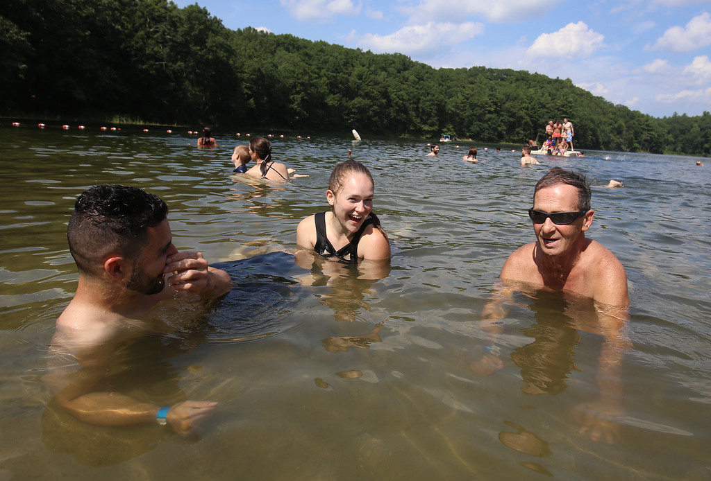 . From left, Nick Rixford, his girlfriend Alana Jones, and his father Donald Rixford, all of Leominster, stay cool lying in shallow water in Mirror Lake in Devens on a hot afternoon. (SUN/Julia Malakie)