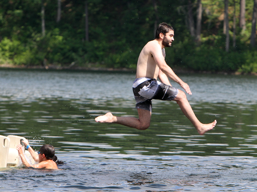 . Daniel Castellon of Ayer jumps off the float at Mirror Lake in Devens on a hot afternoon. (SUN/Julia Malakie)