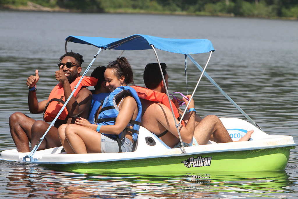 . From left front, Yvon Gachette and Kira Mengistu, both of Cambridge, Harry Brar of Boston, and Roland Hence of Cambridge (rear), go for a paddle boat ride at Mirror Lake in Devens on a hot afternoon. (SUN/Julia Malakie)