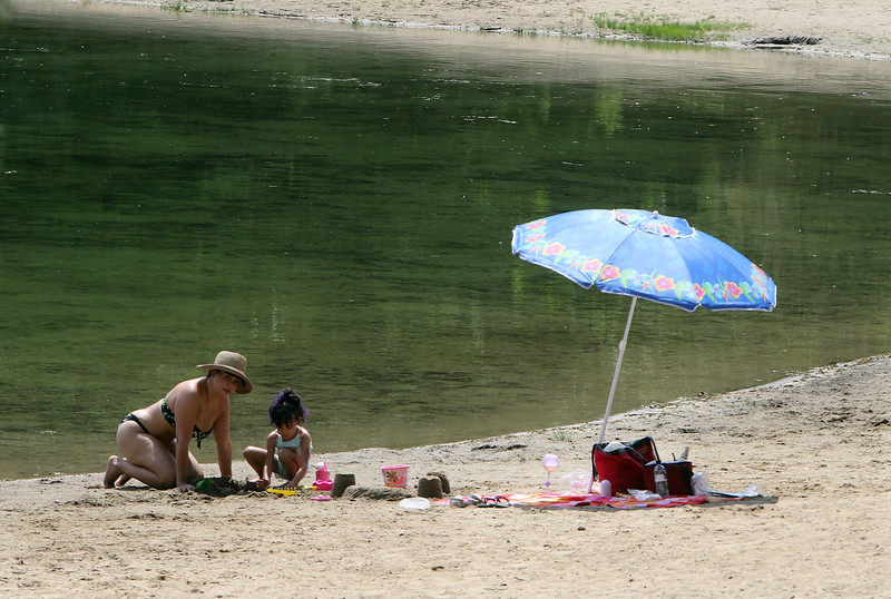 Edith Garrea and her goddaughter Jeralisse Garay, 5, both of Fitchburg, cool off at Mirror Lake in Devens, during a hot spell.  SUN/Julia Malakie