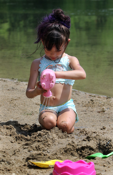 Jeralisse Garay, 5, of Fitchburg, washes off sand at Mirror Lake in Devens on a visit with her godmother, during a hot spell.  SUN/Julia Malakie