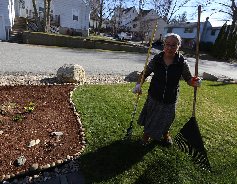 Gil gathers up rakes after working with her mother Tina on their garden on Beacon Street in Lowell. [Note: Gil didn't want to give last names] JULIA MALAKIE/LOWELLSUN