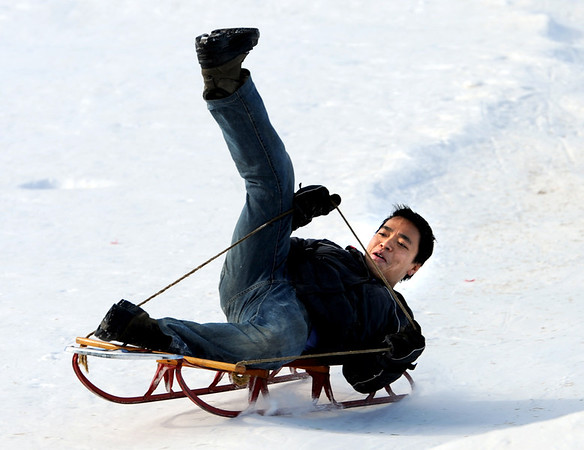 "Bayu Arjana, a former native of Indonesia, flies down the hill with a vintage sled on Tuesday.<br /> No school and plenty of snow at Scott Carpenter Park in Boulder, equals sledding.<br /> For a video and more photos of sledding, go to  <a href=""http://www.dailycamera.com"">http://www.dailycamera.com</a>.<br /> December 27, 2011 / Cliff Grassmick"