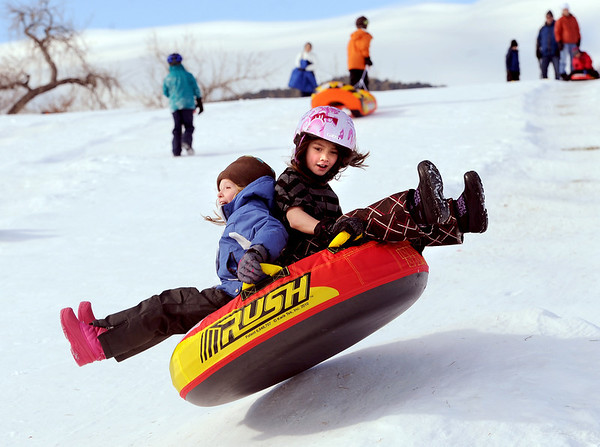 "Rowan Ellis-Rissler, left, and Darcy Jew, fly over a bump at Scott Carpenter Park on Tuesday.<br /> No school and plenty of snow at Scott Carpenter Park in Boulder, equals sledding.<br /> For a video and more photos of sledding, go to  <a href=""http://www.dailycamera.com"">http://www.dailycamera.com</a>.<br /> December 27, 2011 / Cliff Grassmick"