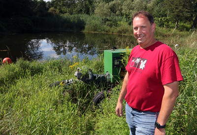 July 28, 2021 - Dave Dumaresq, owner of Farmer Dave's, at his Dracut location. The recent heavy rains have been beneficial, reducing irrigation needs and filling the irrigation pond, rear, in contrast to last year's drought.  SUN/Julia Malakie