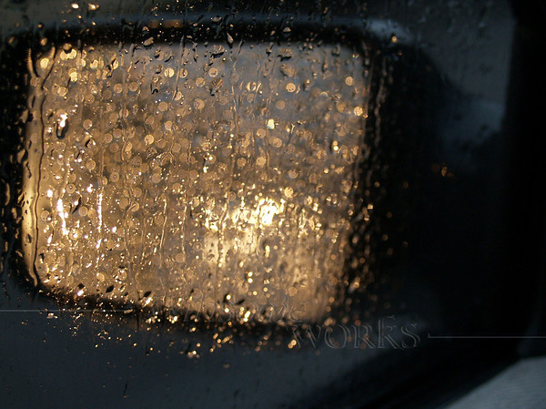 Car mirror on rainy day with reflected headlights