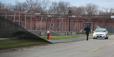 An Elyria Police officer looks over a large section of fence that was ripped down by the heavy winds that blew through the area Monday. The fence on the old Moen property now occupied by Leggett and Platt blew down on the Foster Avenue side of the property. BRUCE BISHOP/CHRONICLE