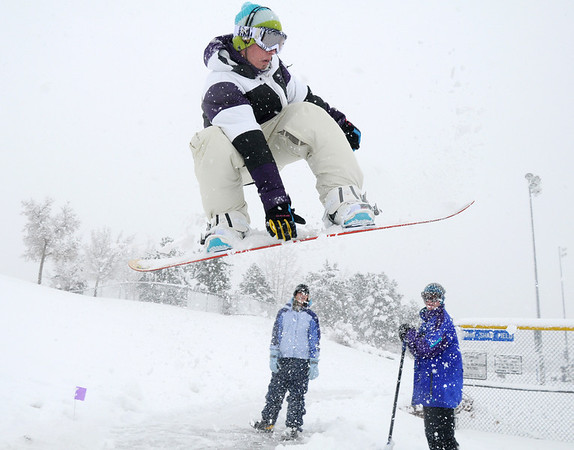Lance Kittel, 16, gets air as he snowboards down a slope at Community Park as fellow Broomfield High friends Kellie Aldridge, 17, left, and Aaron Corbet, 16, watch on Wednesday. <br /> October 28, 2009<br /> Staff photo/David R. Jennings