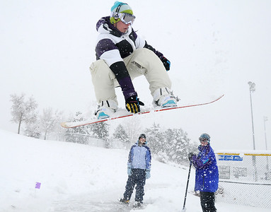 Lance Kittel, 16, gets air as he snowboards down a slope at Community Park as fellow Broomfield High friends Kellie Aldridge, 17, left, and Aaron Corbet, 16, watch on Wednesday.  October 28, 2009 Staff photo/David R. Jennings