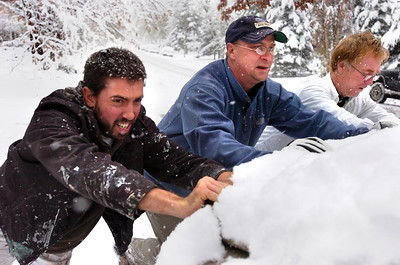 SNOW2.JPG From left to right Chris Norman, Tom Fraser, and Don Snyder help push out a friend  whose car was stuck on University Hill in Boulder. Photo by Paul Aiken / The Camera / Oct 28, 2009