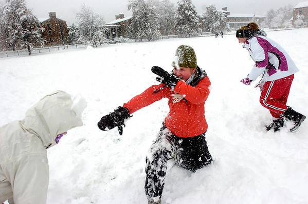 Laine Smith, in center, hits Kaylyn Bopp on the head with a snowball while fellow CU freshman Hailee Durand right runs away on Farrand Field on the CU Boulder Campus Wednesday afternoon.<br /> Photo by Paul Aiken / The Camera / Oct 28, 2009