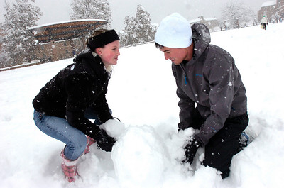 Christine Reever, left and Ben Wise work together to build a snowman on Farrand Field on the CU Boulder Campus Wednesday afternoon. Wise, who is from Texas, said he'd never seen this much snow in his life. Photo by Paul Aiken / The Camera / Oct 28, 2009