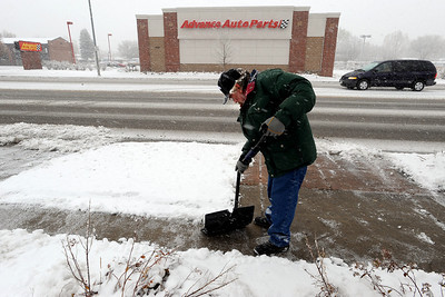 Ray Barber shovels the sidewalk at the 1400 block of Main Street in Longmont on Wednesday. Cliff Grassmick / October 29, 2009