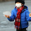 Ice skating at the pond at Roberts Field in Chelmsford. From left, Anderson Zhu, 6, of Acton, collects pieces of ice from the edge of the pond during a visit to Roberts Field with his mother and brother. (SUN/Julia Malakie)