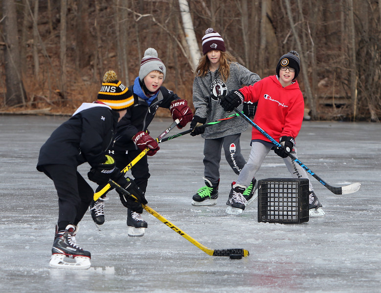 Ice skating at the pond at Roberts Field in Chelmsford.  From left, friends Connor O'Donnell, 11, Andrew Migala, 9, Elizabeth Johnson, 9, and Liam Dowd, 10, all of Chelmsford, who all play Chelmsford Youth Hockey, get in some skating on a free afternoon. It was a normal, non-Covid related half day of school. (SUN/Julia Malakie)