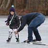Ice skating at the pond at Roberts Field in Chelmsford. Kenny LaBrecque of Chelmsford helps his daughter Annika LaBrecque, 6, with her shin guards. Annika is starting a girls hockey program this year. (SUN/Julia Malakie)