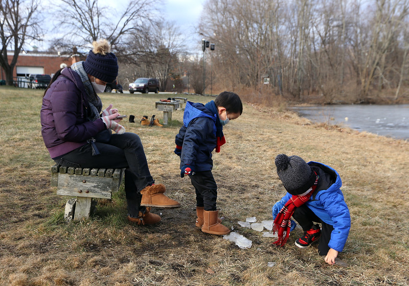 Ice skating at the pond at Roberts Field in Chelmsford. From from right, Anderson Zhu, 6, of Acton, collects pieces of ice from the edge of the pond during a visit to Roberts Field with his brother Ethyn  Zhu, 3, who was stomping on the pieces, and their mother Ming Jiao. (SUN/Julia Malakie)