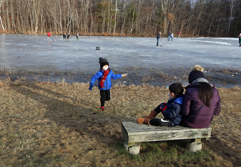 Ice skating at the pond at Roberts Field in Chelmsford. From left, Anderson Zhu, 6, of Acton, collects pieces of ice from the edge of the pond during a visit to Roberts Field with his brother Ethyn  Zhu, 3, and their mother Ming Jiao. (SUN/Julia Malakie)