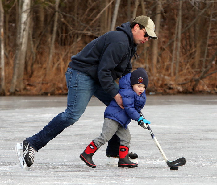 Ice skating at the pond at Roberts Field in Chelmsford. Kenny LaBrecque of Chelmsford helps his son Jake, 3, swing a full size hockey stick. (SUN/Julia Malakie)