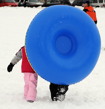 "Ria Yankee, left, and her mother Jann, are eclipsed by their tube after a day of sledding.<br /> It was another big sledding day at Scott Carpenter Park on Sunday.<br /> For more sledding photos, go to  <a href=""http://www.dailycamera.com"">http://www.dailycamera.com</a>.<br /> Cliff Grassmick / November 15, 2009"