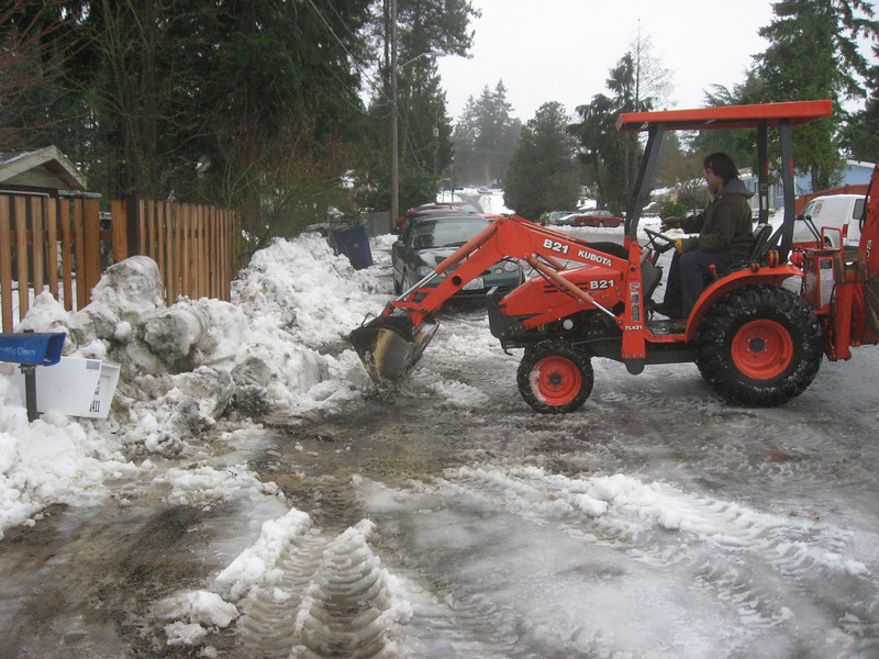My neighbor, John, and his Kubota clearing a way for us to park and remove our cars.  The fence is 5' tall to give a reference for the snow piles.  It is extremely wet snow and leads to high centering of the cars if not removed.