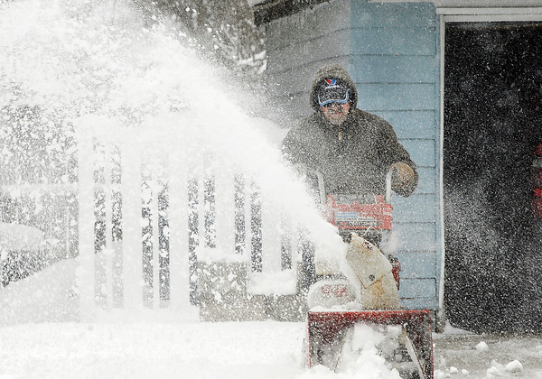 With the gusty winds Don Shanks sometimes got some of the remnants of his snowblowing efforts back at him as he cleaned a driveway along west Vineyard Street Monday.