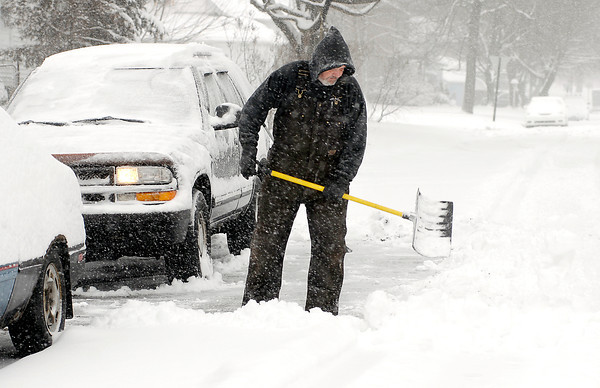 As snow continued to fall Monday morning Mike Robison was busy digging out his vehicles along East 9th Street.
