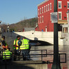 Village work crew pumping water from Cinderella Shop basement into the river. Note water level at Broadway bridge