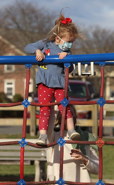 Features at Veterans Memorial Park in Dracut. Thea Karabatsos, 3, of Dracut, reaches the top of a climbing structure with help from her mother Maureen Karabatsos.   JULIA MALAKIE/LOWELLSUN