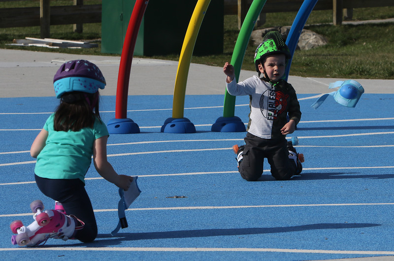 Features at Veterans Memorial Park in Dracut. Owen Keyes, 4, and his sister Olivia, 6, of Dracut, go roller skating on the slightly softer surface of the water park. Owen had decided he didn't want to wear his knee pads. JULIA MALAKIE/LOWELLSUN