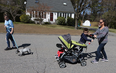Spring weather features in Leominster. Sarah Marro, left, walking her 14-week-old Lab/blue heeler puppy, Scout, and her mother Donna Woodward, pushing stroller with Marro's daughter Ava-Jane, 1, and son Braden, 4, all of Leominster, go for a walk around their neighborhood on a warm spring day. JULIA MALAKIE/LOWELLSUN