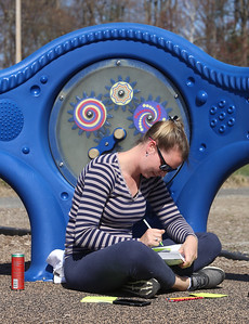 Spring weather features in Leominster. Erika [who didn't want to give last name or town], an LPN and  student at Wachusett Community College, works on flash cards for a class while her child plays at Fournier Park in Leominster. She's studying to become an R.N.  JULIA MALAKIE/LOWELLSUN