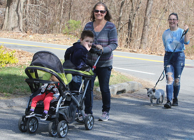 Spring weather features in Leominster. Donna Woodward, center, her daughter Sarah Marro, right, walking her 14-week-old Lab/blue heeler puppy, Scout, and Marro's daughter Ava-Jane, 1, and son Braden, 4, all of Leominster, go for a walk around their neighborhood on a warm spring day. JULIA MALAKIE/LOWELLSUN