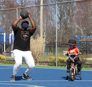 Spring weather features in Leominster. Hakeem Joseph of Clinton shoots baskets while his son Kahmari Joseph, 4, practices riding his bike with training wheels at Fournier Park in Leominster.  JULIA MALAKIE/LOWELLSUN