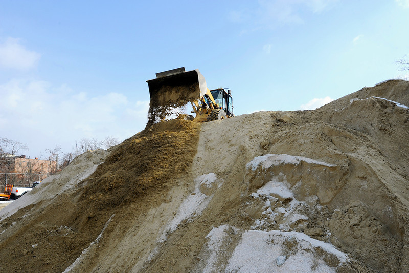 A Fitchburg DPW front-end-loader dumps sand to the front of the pile for easy access later on in preparation for the snowstorm this weekend, Friday.<br /> SENTINEL & ENTERPRISE / BRETT CRAWFORD