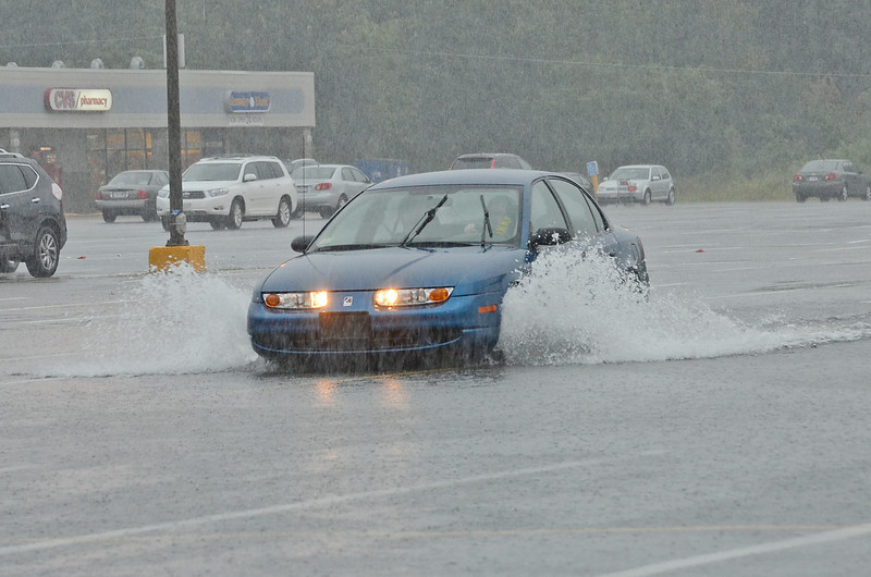 A car drives through the flooded parking lot on John Fitch Highway in Fitchburg on Wednesday afternoon during a flash flood warning. SENTINEL & ENTERPRISE / ASHLEY GREEN