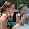 Rebecca Rector, 11, of Clinton, tries to keep cool while eating ice cream as friend Crystalyn Crowe, 10, of Clinton, takes a break from swimming at Riverview Pool. • Scott Levine/Clinton Herald