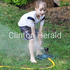 Cool water from a sprinkler kept Alex McClung, 5, of Clinton, busy in the afternoon as temperatures neared the 100-degree mark. • Scott Levine/Clinton Herald