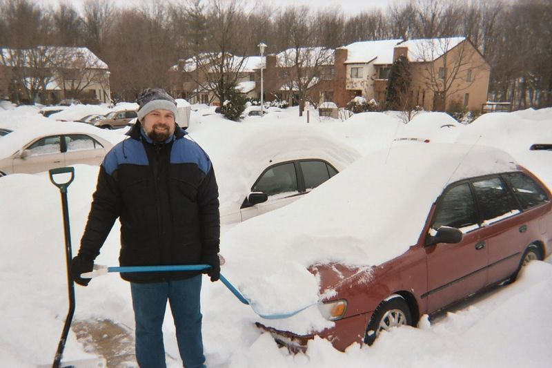 Ken worked to dig out the cars. He's found the red one and begun to clear a path alongside it.