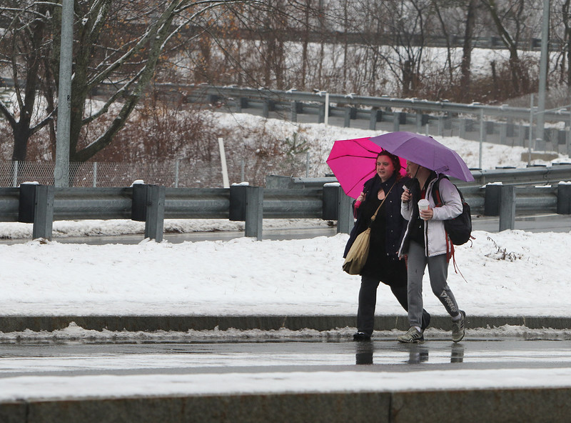 Iris Soran of Brighton, left, and her friend Patricia Hiort of Lowell walk along Thorndike Street in Lowell in a mix of snow and rain. (SUN/Julia Malakie)