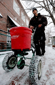 Lance Rouse, of the City of Boulder Parks and Recreation, puts down crystals to melt the ice on Pearl Street. People in downtown Boulder go about their day during a Valentine's Day snow on Thursday. For more snow photos and a video, go to www.dailycamera.com.  Cliff Grassmick  / February 14, 2013