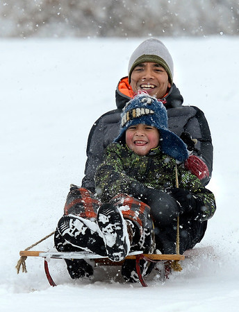 "Bayu Rajana of Boulder and his son Milo, 8, rocket down the hill at Scott Carpenter Park in a carpet of freshly fallen snow on Thursday February 14, 2013.<br /> For more photos and a video of the snow go to  <a href=""http://www.dailycamera.com"">http://www.dailycamera.com</a><br /> Photo by Jeremy Papasso."
