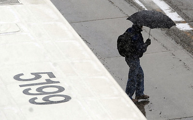 A pedestrian crosses 14th Street after leaving the downtown bus station. People in downtown Boulder go about their day during a Valentine's Day snow on Thursday. For more snow photos and a video, go to www.dailycamera.com.  Cliff Grassmick  / February 14, 2013