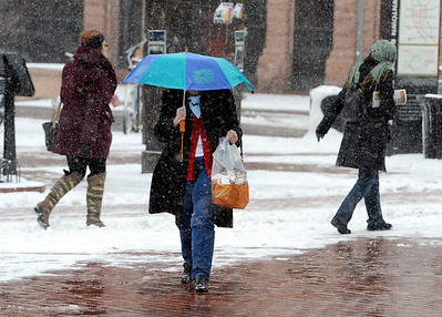 Kathy Herrmann uses an umbrella to walk back to work at the  downtown courthouse on Pearl Street. People in downtown Boulder go about their day during a Valentine's Day snow on Thursday. For more snow photos and a video, go to www.dailycamera.com.  Cliff Grassmick  / February 14, 2013