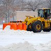 A large front-end-loader plows snow, ice, and slush from the parking lot at the Mall at Whitney Field in Leominster on Monday.<br /> SENTINEL & ENTERPRISE / BRETT CRAWFORD