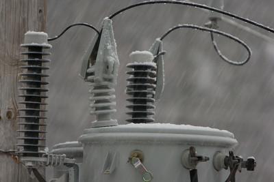 Snow falling on a transformer.
